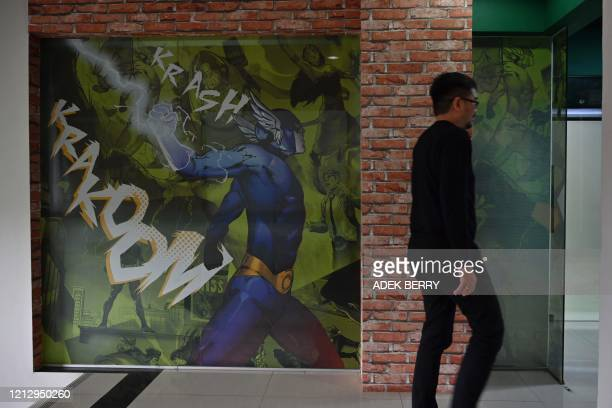 This picture taken on February 4 2020 shows a man walking past a wall featuring amination characters at the office of Indonesian company Bumilangit...
