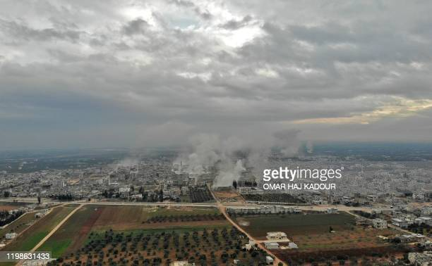 This picture taken on February 4, 2020 shows an aerial view of smoke plumes billowing from bombardment by the Syrian government forces and allies on...
