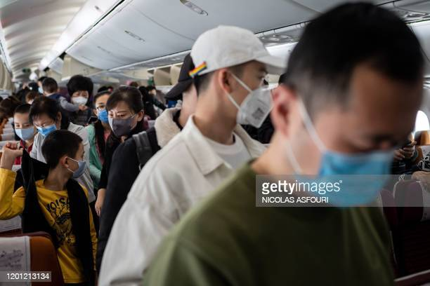 This picture taken on February 4, 2020 shows passengers wearing protective face masks as they prepare to disembark at Bangkok's Suvarnabhumi...