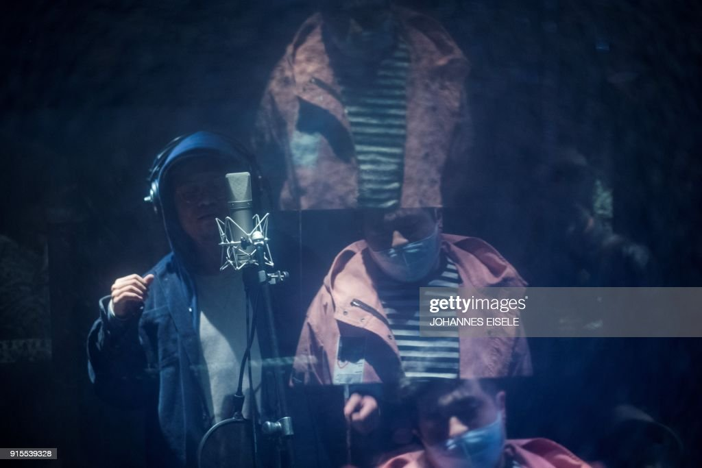 This picture taken on February 5, 2018 shows Shanghai rapper Naggy (L) singing in his studio while fellow rapper Mr Trouble, Hong Tianlin (R), is reflected in the studio window in Shanghai. Chinese rap and hip hop seemed poised to break out after a wildly popular singing show, but an abrupt backlash has tamed the swagger of artists who fear the music scene will be nipped in the bud by Communist politics. / AFP PHOTO / Johannes EISELE / TO GO WITH China-culture-music-rap-censorship,FOCUS by Dan Martin
