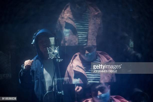 This picture taken on February 5 2018 shows Shanghai rapper Naggy singing in his studio while fellow rapper Mr Trouble Hong Tianlin is reflected in...
