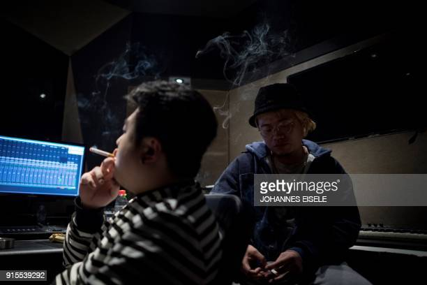 This picture taken on February 5 2018 shows Shanghai rappers Naggy and Mr Trouble Hong Tianlin smoking in their studio in Shanghai Chinese rap and...