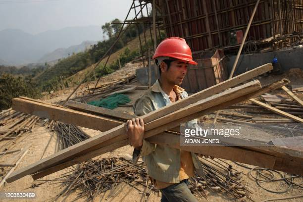This picture taken on February 8 2020 shows a Chinese worker carrying materials for the first rail line linking China to Laos a key part of Beijing's...