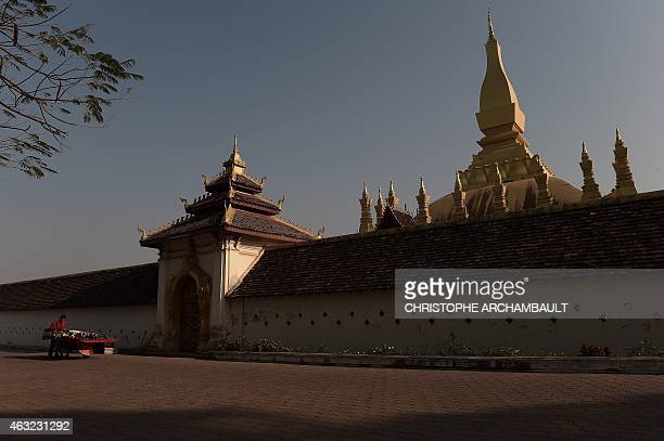 This picture taken on February 9 2015 shows a souvenir vendor pushing his cart outside the That Luang stupa in Vientiane The That Luang a goldcovered...