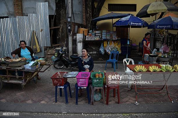 This picture taken on February 9 2015 shows street food vendors waiting for customers in downtown Vientiane AFP PHOTO / Christophe ARCHAMBAULT