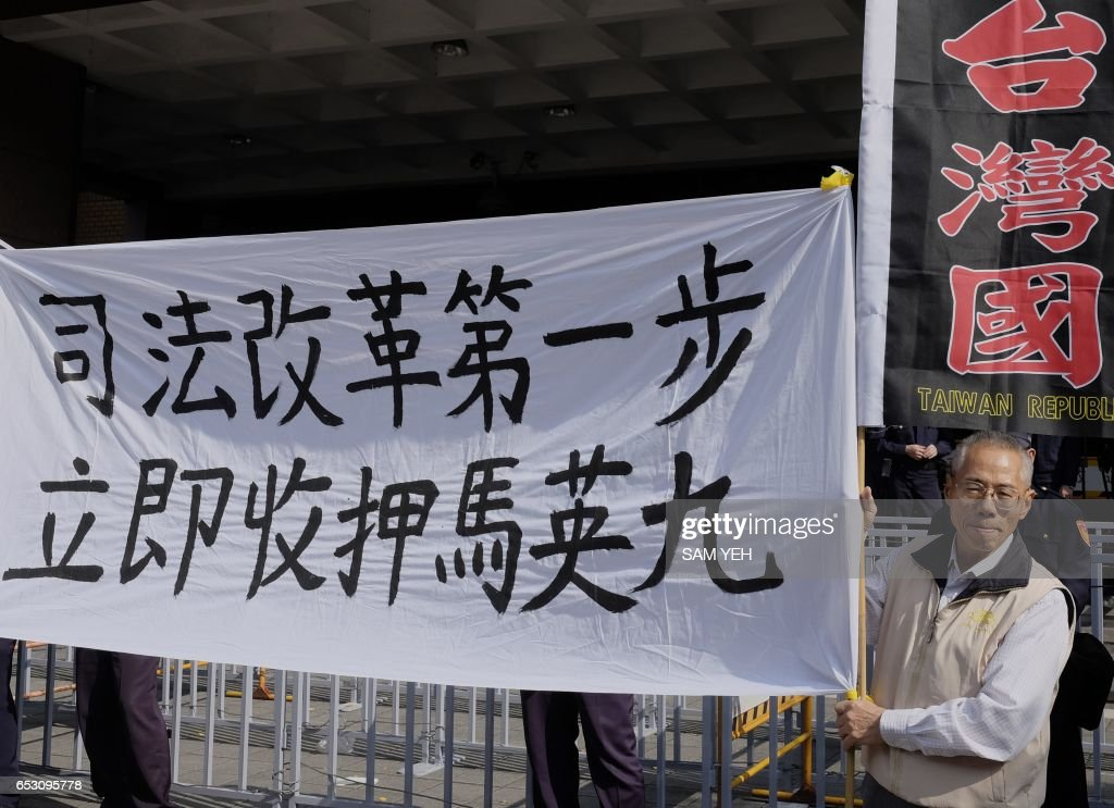 This picture taken on January 10, 2017 shows a pro-Taiwan independence activist displaying a banner that reads 'First step to reform, put Ma Ying-jeou in custody' outside the Taipei District Court. Taiwan's former president Ma Ying-jeou was slapped with new charges on March 14 in a political leaks controversy, just weeks before he faces possible conviction in another related case. / AFP PHOTO / Sam YEH