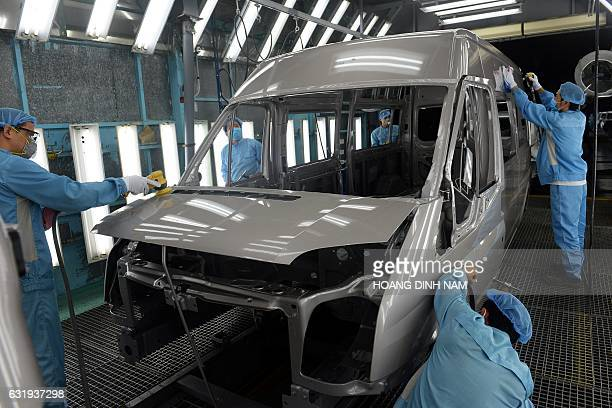 This picture taken on January 11 2017 shows Vietnamese employees in the painting shop at the Ford automotive plant in the northern province of Hai...