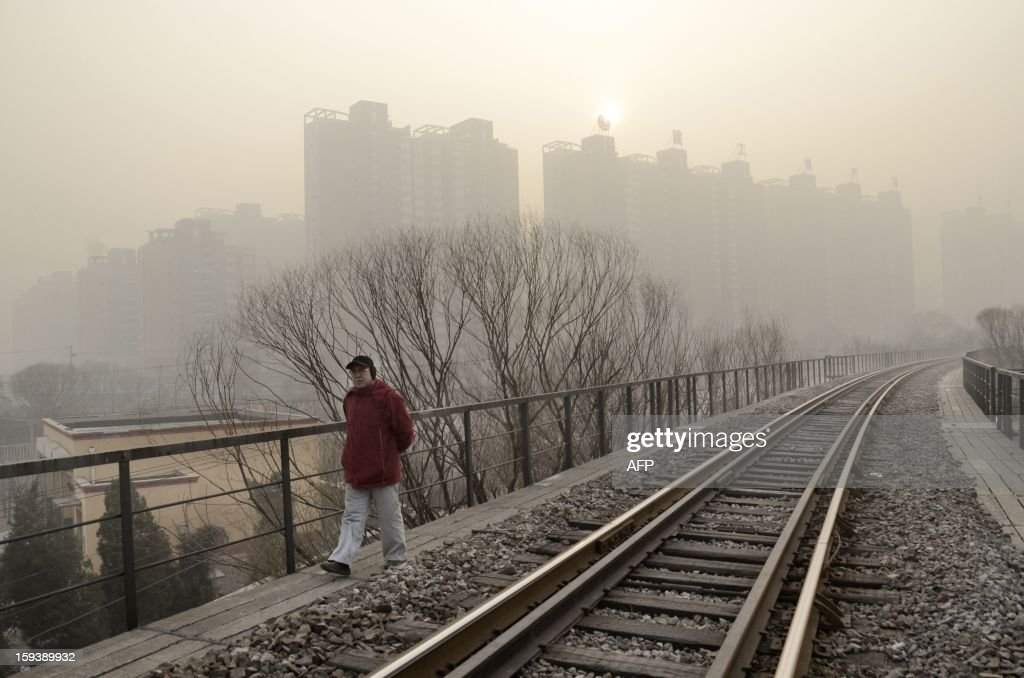 This picture taken on January 12, 2013 shows a Chinese man walking along a railway track in Beijing. Dense smog shrouded Beijing on January 12, with pollution at hazardous levels for a second day and residents advised to stay indoors, state media said.