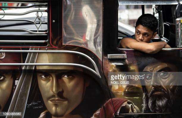 This picture taken on January 13 2019 shows custom artwork on the side of a jeepney as a driver's assistant waits for passengers during rush hour in...