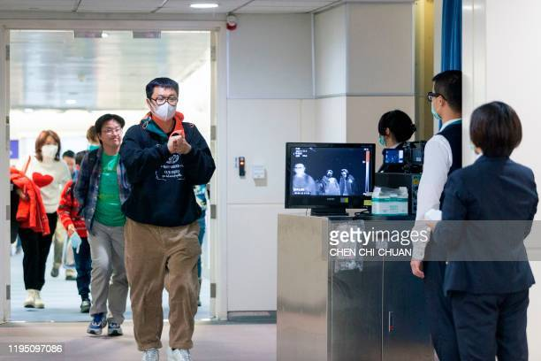 This picture taken on January 13, 2020 shows Taiwan's Center for Disease Control personnel using thermal scanners to screen passengers arriving on a...