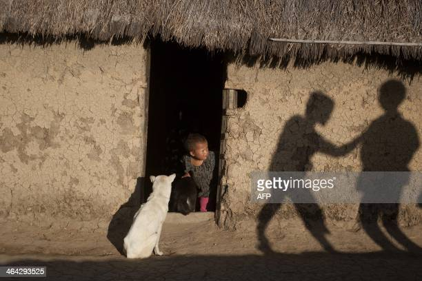This picture taken on January 15 2014 shows a girl peering outside her hut at a village in Mantong township in Myanmar's northern Shan state an area...