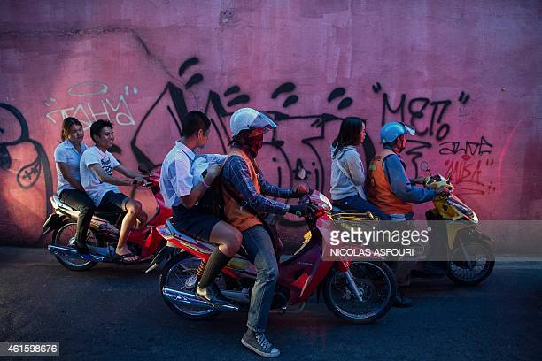 This picture taken on January 15 2015 shows people riding motorbikes in Bangkok Thailand's economy grew at a lacklustre 06 percent in the third...