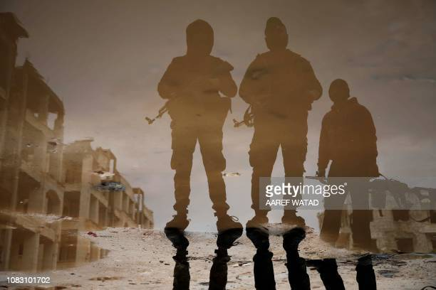 TOPSHOT This picture taken on January 15 2019 shows a reflection of Syrian fighters from the Turkishbacked National Liberation Front as they stand...