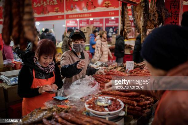This picture taken on January 15 2020 shows a vendor selling dried sausages to customers at a market in Beijing The World Health Organisation said on...