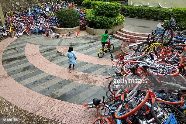 This picture taken on January 16 2017 shows rented bicycles from bikesharing firms near the entrance of Xiashan park in Shenzhen Guangdong province...