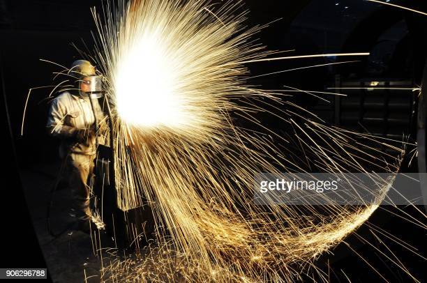 TOPSHOT This picture taken on January 17 2018 shows a Chinese worker cutting steel in Qingdao in China's eastern Shandong province on January 18 2018...