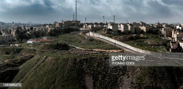 This picture taken on January 17 2019 from the Palestinian West Bank village of AlRam shows the controversial Israeli separation barrier separating...