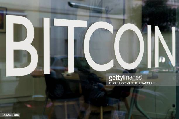 This picture taken on January 17 shows a bitcoin logo on a window at La Maison du Bitcoin in Paris / AFP PHOTO / GEOFFROY VAN DER HASSELT