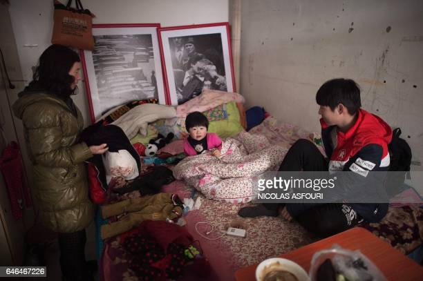 This picture taken on January 18 2017 shows a family inside their tiny shared room in the Heiqiaocun migrant village in Beijing China's capital...