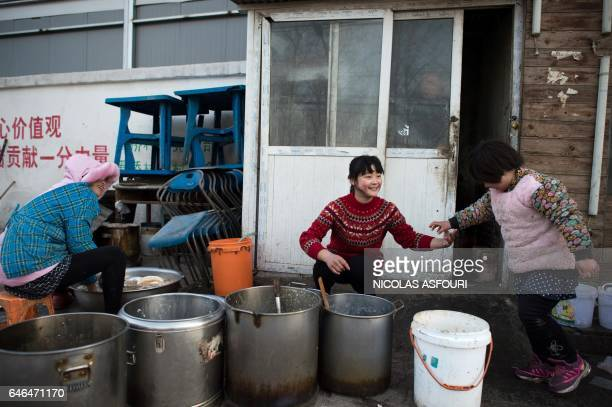 TOPSHOT This picture taken on January 18 2017 shows workers cleaning dishes outside a restaurant in the Heiqiaocun migrant village in Beijing China's...