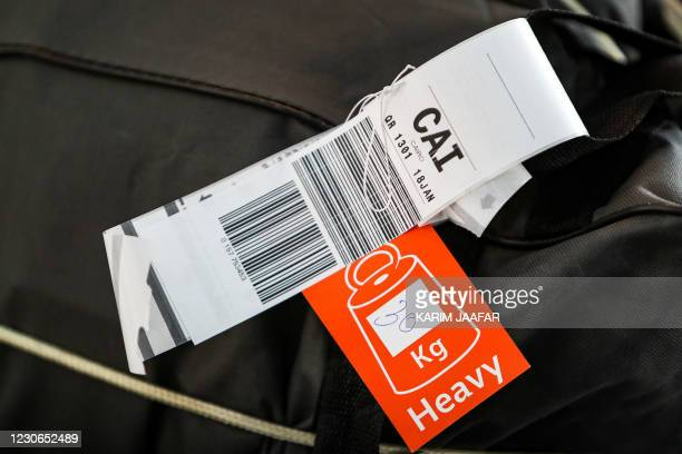 This picture taken on January 18, 2021 shows a luggage tag on a suitcase being transported on the first flight between Doha and Cairo after the...