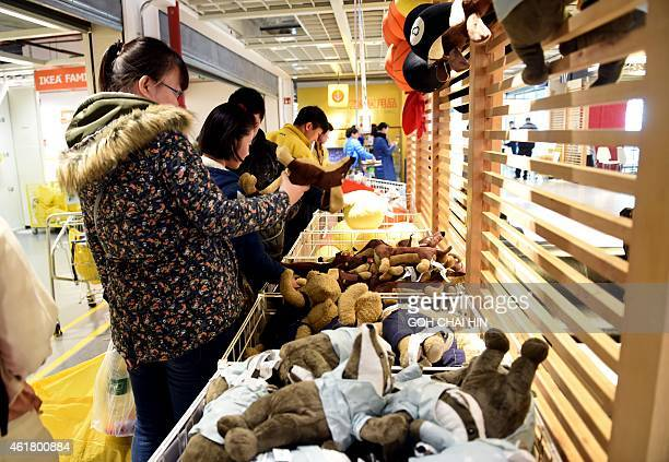 This picture taken on January 19 2015 shows Chinese shoppers buying various soft toys at a furniture store in Beijing China's gross domestic product...