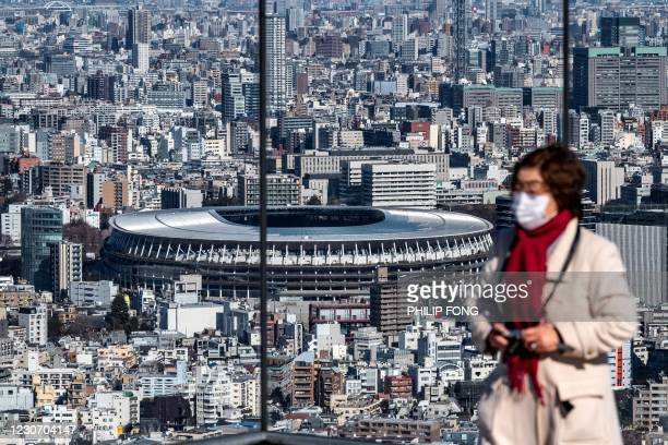 This picture taken on January 19, 2021 shows the National Stadium , the main venue for the Tokyo 2020 Olympic and Paralympic Games, from the Shibuya...