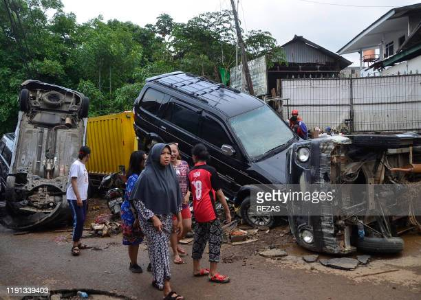TOPSHOT This picture taken on January 2 2020 shows residents walking past destroyed cars in Bekasi West Java after flooding triggered by heavy rain...