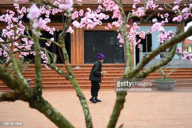 This picture taken on January 20 2019 shows a leprosy survivor leaving a pagoda after offering prayers in Van Mon Leprosy hospice compound northern...