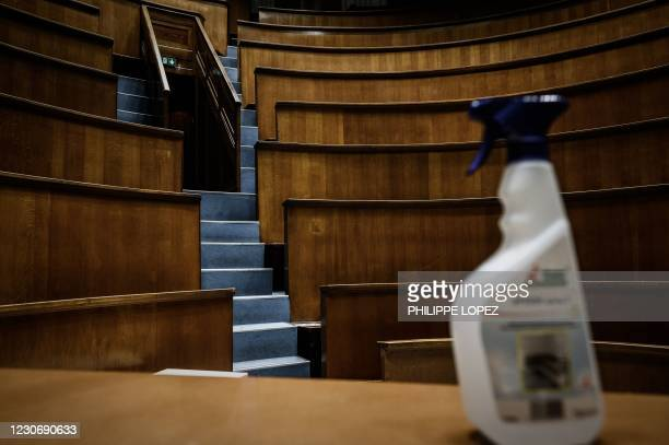 This picture taken on January 20, 2021 in Bordeaux, southwestern France, shows a bottle disinfectant spray on a desk of the empty auditorium at the...