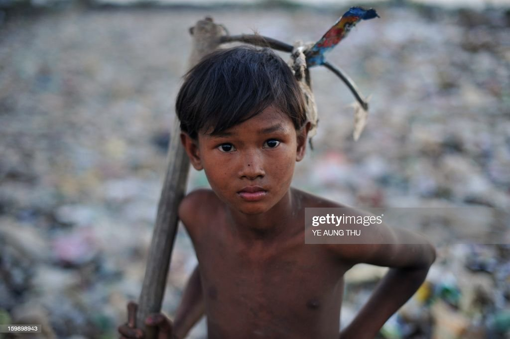 This picture taken on January 22, 2013 shows a Myanmar boy holding a tool he uses to collect material for sale and recycling at a waste dump on the outskirts of Yangon. Myanmar is one of the poorest countries in Asia after decades of economic mismanagement and isolation under army rule, but could become Asia's next economic engine if it enacts vast reforms, the IMF said in November of 2012. AFP PHOTO / Ye Aung THU