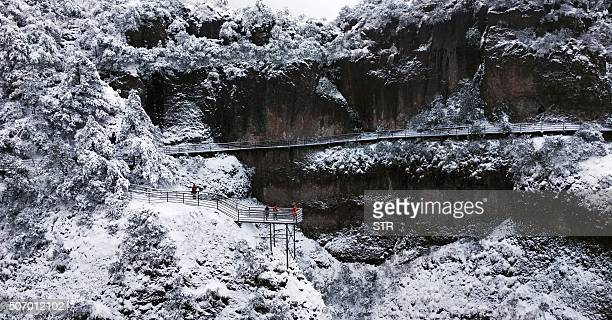 This picture taken on January 23 2016 shows tourists taking pictures of the snow on Shenxianju Mountain near the city of Taizhou in eastern China's...
