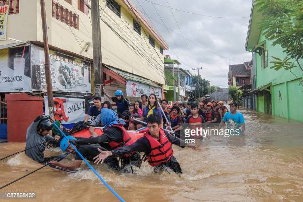 This picture taken on January 23, 2019 shows residents evacuating their homes in Makassar as heavy rain and strong winds pounded the southern part of...