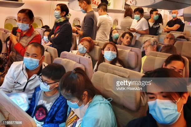 This picture taken on January 23, 2020 shows passengers wearing masks prepare to disembark from a flight from Hong Kong on arrival at Bangkok's...