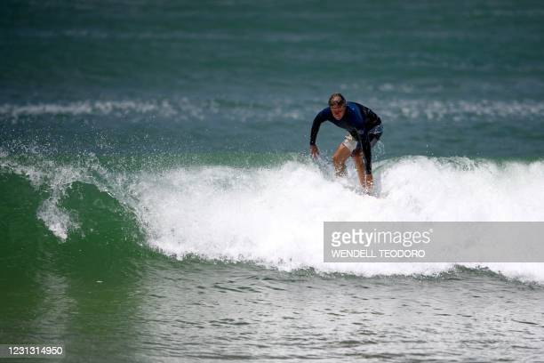 This picture taken on January 23, 2021 shows Bruce Lucas, an Australian shark attack survivor, surfing on Crowdy Bay National Park at Port Macquarie,...