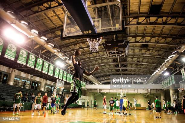 TOPSHOT This picture taken on January 24 2017 shows Cameroon's Benoit Mbala attempting to dunk the ball during a basketball practice session at De La...
