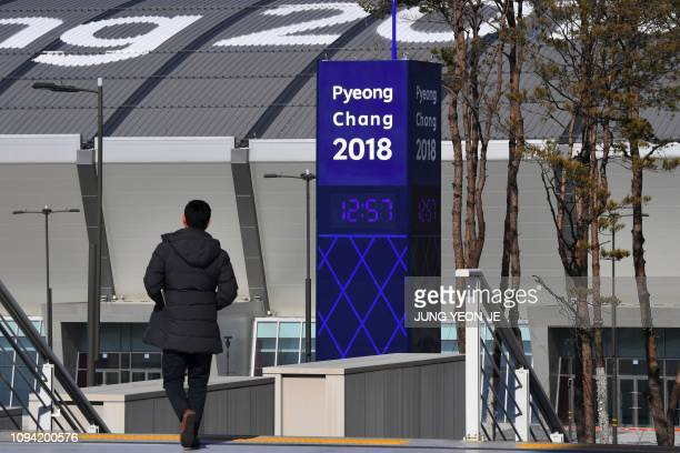 This picture taken on January 24 2019 shows a man walking past a signboard for the Pyeongchang 2018 Winter Olympic Games at the Gangneung Olympic...