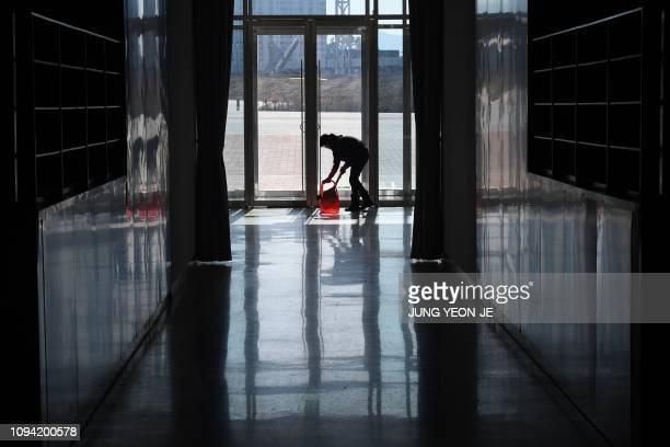 This picture taken on January 24 2019 shows a worker cleaning the floor in the Gangneung Oval where the speed skating was held during the Pyeongchang...