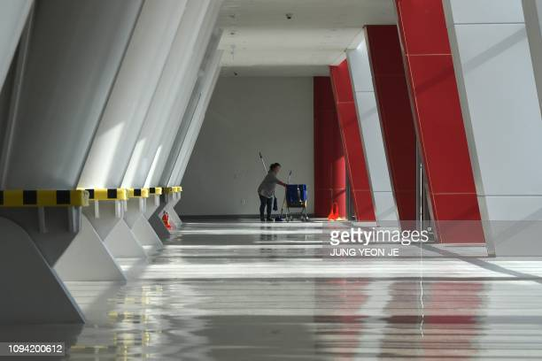 This picture taken on January 24 2019 shows a worker cleaning the floor in the Gangneung Oval where the speedskating was held during the Pyeongchang...