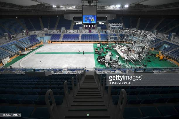 This picture taken on January 24 2019 shows workers setting up a stage for a music concert in the Gangneung Ice Arena where the figure skating and...