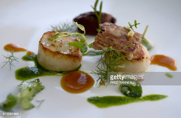 This picture taken on January 25 2018 shows a dish of 'tripier marin' seared scallops with black pudding and pig's feet broth garnished with...