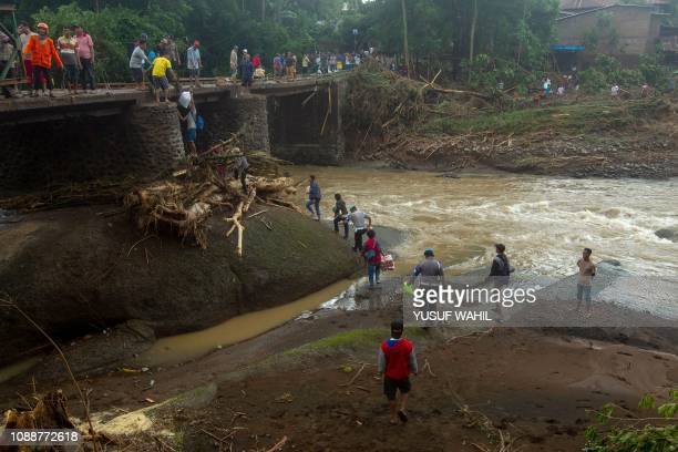 This picture taken on January 25, 2019 shows Indonesian rescuers repairing a bridge after a landslide in Gowa, after heavy rains and strong winds...