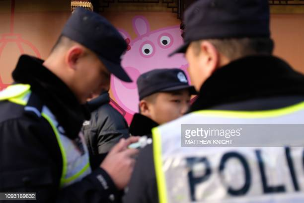 This picture taken on January 25 2019 shows police patrolling past a Peppa Pig figure on a wall outside the Yu Yuan gardens a popular tourist spot...