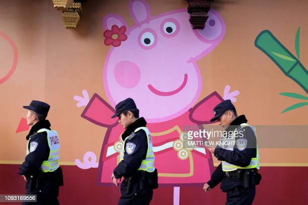 TOPSHOT This picture taken on January 25 2019 shows police walking past a Peppa Pig figure on a wall outside the Yu Yuan gardens a popular tourist...