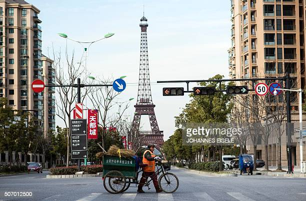 This picture taken on January 26, 2016 shows a street clearn crossing the street in front of a replica of the Eiffel Tower in Tianducheng, a luxury...