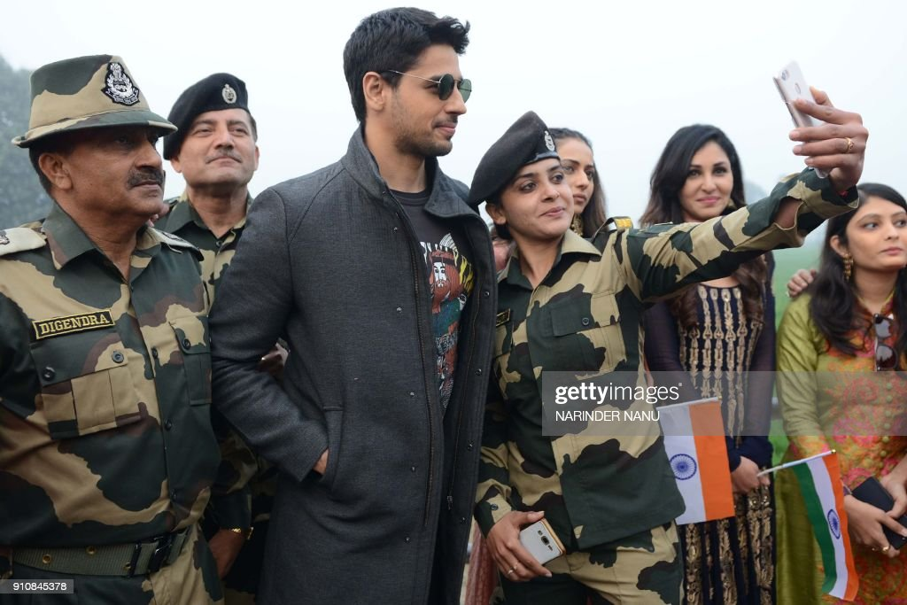 This picture taken on January 26 shows Indian actors Sidharth Malhotra along with BSF personnel taking selfie pictures during a promotional event for.