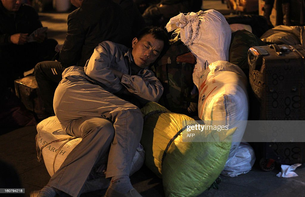 This picture taken on January 28, 2013 shows a man sleeping on his luggage at Guangzhou train station, waiting for his train to go back home for the Lunar New Year, or Spring Festival. Passengers will log 220 million train rides during the 40-day travel season as they criss-cross the country to celebrate with their families, but just as making the trip home can be laborious -- often lasting one or two days -- so can simply acquiring a seat on the train, and every year complaints arise about the inefficiency or unfairness of the system, although an initiative allowing travelers to purchase tickets online aims to curb long queuing times. CHINA