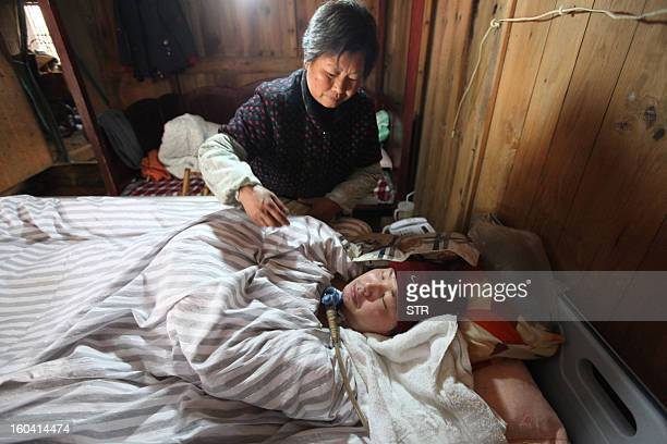 This picture taken on January 28 2013 shows Fu Xuepeng a former mechanic who was paralyzed in a road accident when he was 23 years old breathing with...