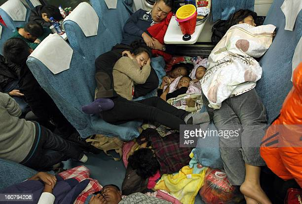 This picture taken on January 28 2013 shows people sleeping on their seats on the train from Guangzhou to Changchun to go back home for the Lunar New...
