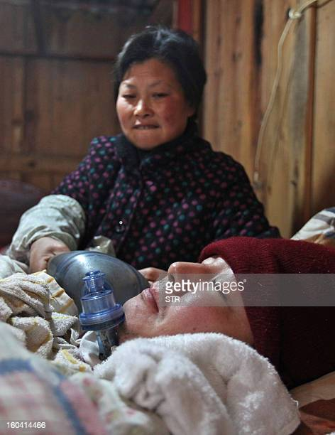 This picture taken on January 28 2013 shows Wang Lanqin compressing a PVC resuscitator pump to help her son Fu Xuepeng a former mechanic who was...